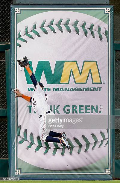 Carlos Gomez of the Houston Astros makes a leaping catch at the wall on a ball hit by Michael Bourn of the Arizona Diamondbacks in the third inning...