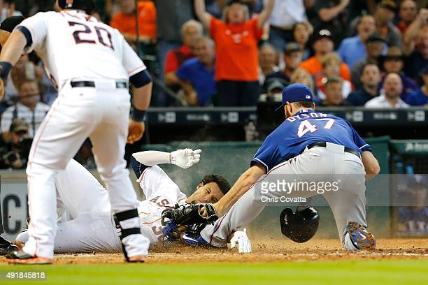 Carlos Gomez of the Houston Astros slides into home against Sam Dyson of the Texas Rangers at Minute Maid Park on September 27 2015 in Houston Texas