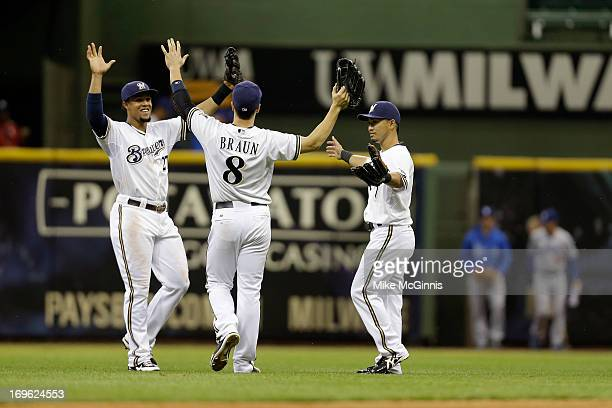 Carlos Gomez of the Milwaukee Brewers celebrates with Ryan Braun and Norichika Aoki after the 5-2 win over the Los Angeles Dodgers at Miller Park on...