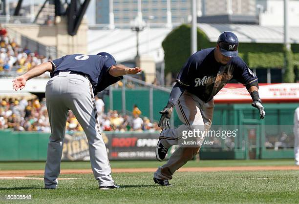Carlos Gomez of the Milwaukee Brewers celebrates with third base coach Ed Sedar after hitting a three run home run in the fourth inning against the...