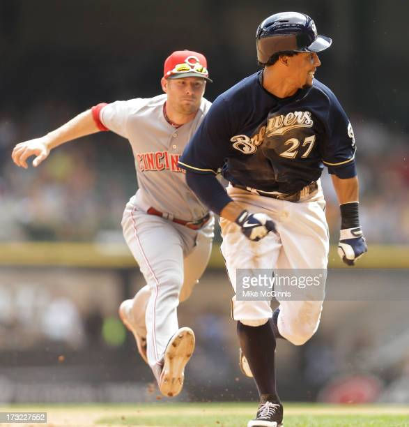 Carlos Gomez of the Milwaukee Brewers gets tagged out in a run down by Zack Cozart of the Cincinnati Reds during the bottom of the fourth inning at...