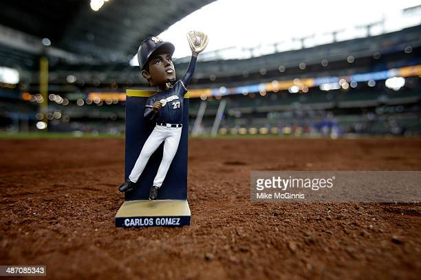 Carlos Gomez of the Milwaukee Brewers golden glove bobble head is displyed on the field before the game against of the Chicago Cubs at Miller Park on...