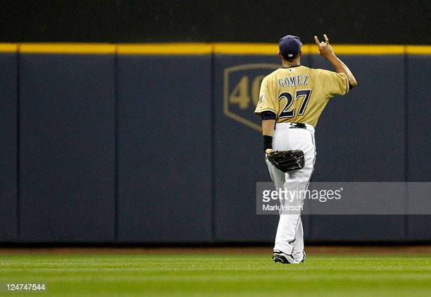 Carlos Gomez of the Milwaukee Brewers makes sign for two outs after making the catch for an out against the Philadelphia Phillies at Miller Park on...