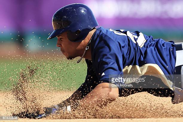 Carlos Gomez of the Milwaukee Brewers slides into second base against the San Francisco Giants during a spring training game at Scottsdale Stadium on...