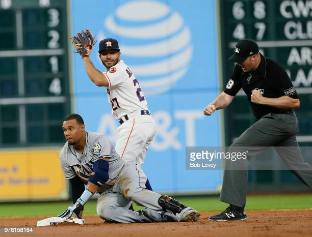 Carlos Gomez of the Tampa Bay Rays is called out trying to stretch a single by second base umpire Nic Lentz as Jose Altuve of the Houston Astros...