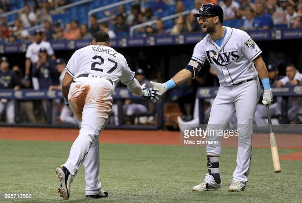 Carlos Gomez of the Tampa Bay Rays is congratulated after scoring by Kevin Kiermaier in the third inning during a game against the Detroit Tigers at...