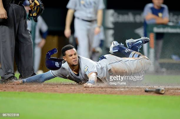 Carlos Gomez of the Tampa Bay Rays slides into home plate and scores in the eighth inning against the Baltimore Orioles at Oriole Park at Camden...