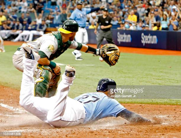 Carlos Gomez of the Tampa Bay Rays slides safely into home for what would turn out to be the winning run in the seventh inning of the game against...