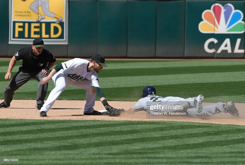Carlos Gomez #27 of the Tampa Bay Rays steals second base sliding past the tag of Jed Lowrie #8 of the Oakland Athletics in the top of the 10th inning at the Oakland Alameda Coliseum on May 28, 2018 in Oakland, California.