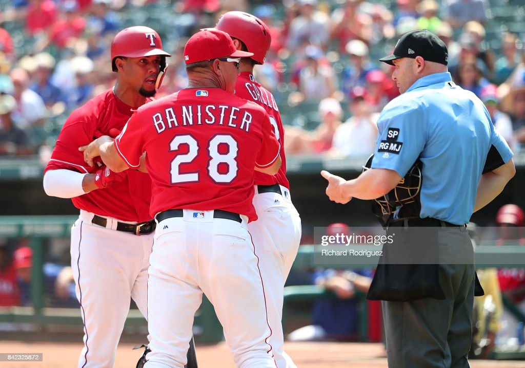Carlos Gomez #14 of the Texas Rangers argues with home plate umpire Mike Estabrook as he is held back by manager Jeff Banister #28 of the Texas Rangers and Joey Gallo #13 of the Texas Rangers after being ejected in the third inning of a game against the Los Angeles Angels of Anaheim at Globe Life Park in Arlington on September 3, 2017 in Arlington, Texas.