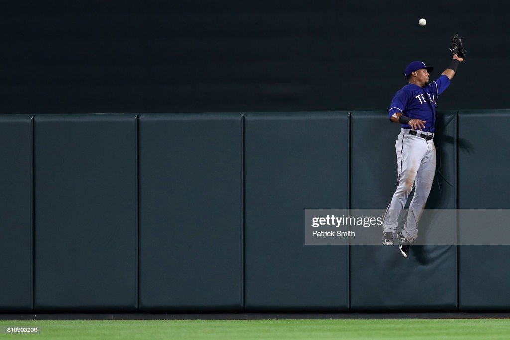 Carlos Gomez #14 of the Texas Rangers cannot make a catch on a home run hit by Seth Smith #12 of the Baltimore Orioles (not pictured) during the seventh inning at Oriole Park at Camden Yards on July 17, 2017 in Baltimore, Maryland.