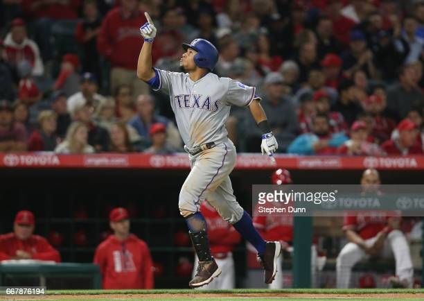 Carlos Gomez of the Texas Rangers celebrates as he runs home after hitting a solo home run in the seventh inning against the Los Angeles Angels of...