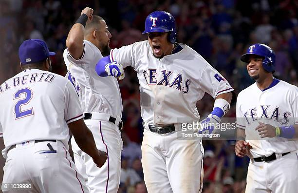 Carlos Gomez of the Texas Rangers celebrates with Rougned Odor of the Texas Rangers and Hanser Alberto of the Texas Rangers after hitting a three run...