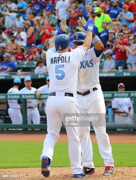 Carlos Gomez of the Texas Rangers congratulates Mike Napoli after scoring on Napoli's home run in the sixth inning against the Seattle Mariners at...