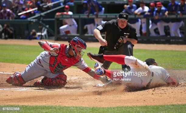 Carlos Gomez of the Texas Rangers is called out at the plate by umpire Bill Miller after being tagged by Martin Maldonado of the Los Angeles Angels...