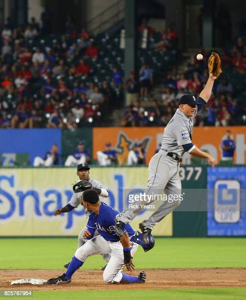Carlos Gomez of the Texas Rangers slides in safe against Kyle Seager of the Seattle Mariners at Globe Life Park in Arlington on August 2 2017 in...