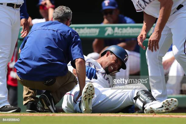 Carlos Gomez of the Texas Rangers winces in pain after rolling his ankle running to first base in the second inning of a game against the New York...