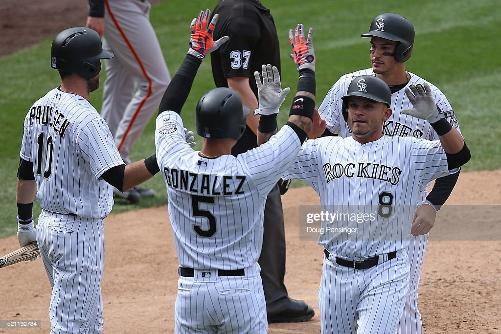 Carlos Gonzalez #5, Gerardo Parra #8 and Nolan Arenado #28 of the Colorado Rockies celebrate with Ben Paulsen #10 after the trio scored on a three RBI double by Mark Reynolds #12 of the Colorado Rockies off of Chris Heston #53 of the San Francisco Giants to take a 8-1 lead in the fifth inning at Coors Field on April 14, 2016 in Denver, Colorado.