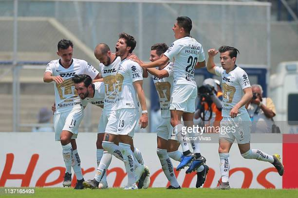 Carlos Gonzalez of Pumas celebrates with teammates after scoring the first goal of his team during the 14th round match between Pumas UNAM and...