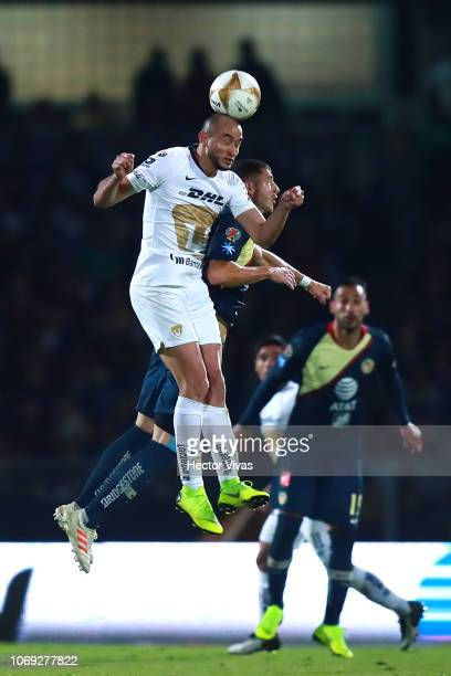 Carlos Gonzalez of Pumas heads the ball against Guido Rodriguez of America during the semifinal first leg match between Pumas UNAM and America as...