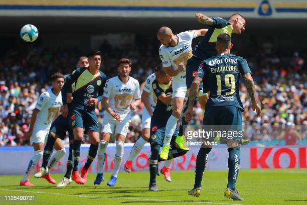 Carlos Gonzalez of Pumas heads the ball to score the first goal of his team against Nicolas Castillo of America during the seventh round match...