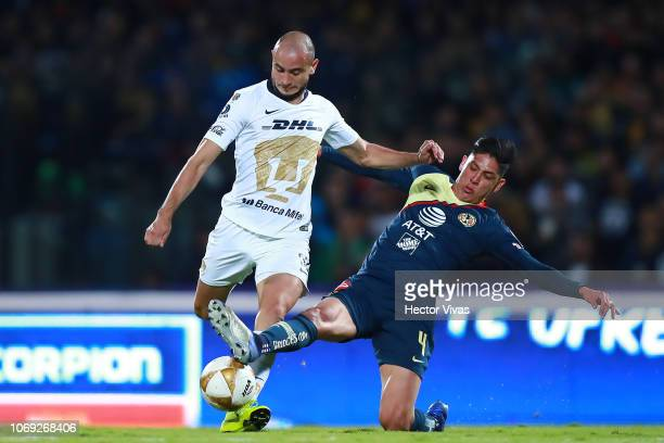 Carlos Gonzalez of Pumas struggles for the ball with Edson Alvarez of America during the semifinal first leg match between Pumas UNAM and America as...
