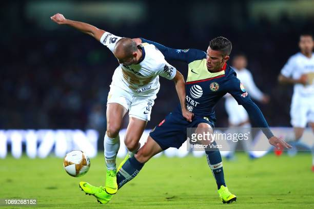 Carlos Gonzalez of Pumas struggles for the ball with Mateus Uribe of America during the semifinal first leg match between Pumas UNAM and America as...