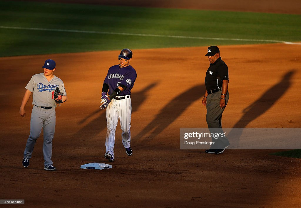 Carlos Gonzalez #5 of the Colorado Rockies arrives at second with a double as second baseman Enrique Hernandez #14 of the Los Angeles Dodgers looks on and umpire Laz Diaz oversees the action during game two of a double header at Coors Field on June 2, 2015 in Denver, Colorado.