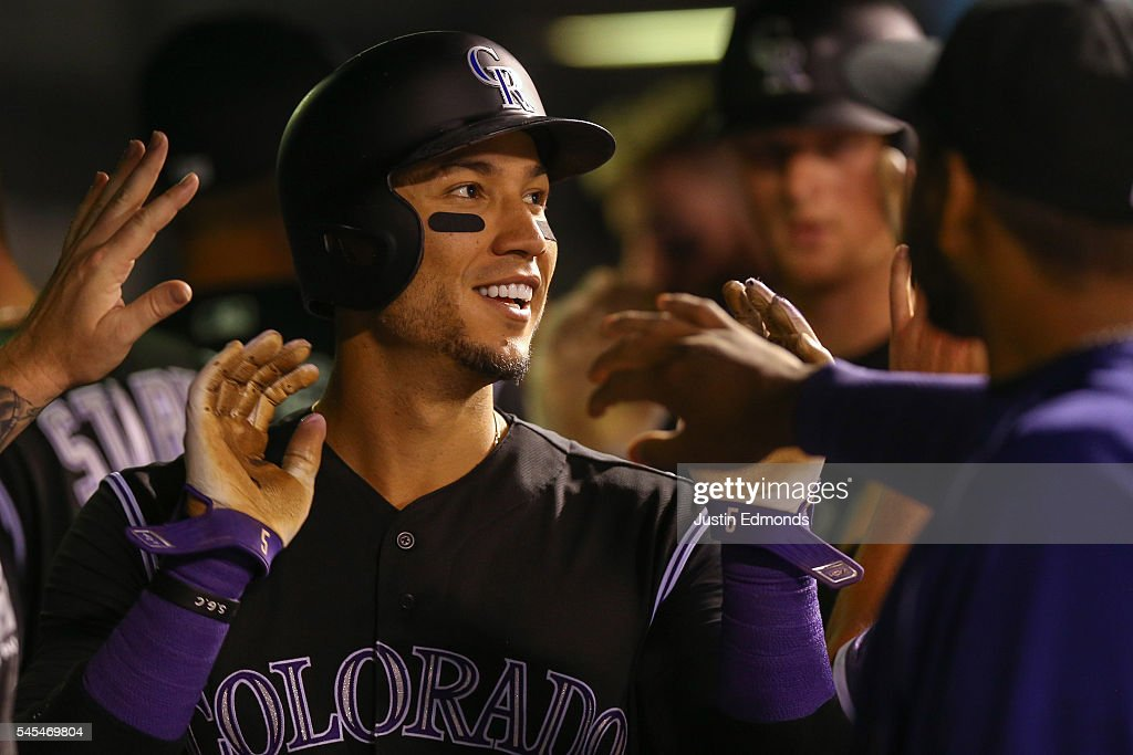 Carlos Gonzalez #5 of the Colorado Rockies celebrates in the dugout after scoring on a three run double off the bat of Mark Reynolds during the seventh inning against the Philadelphia Phillies at Coors Field on July 7, 2016 in Denver, Colorado.