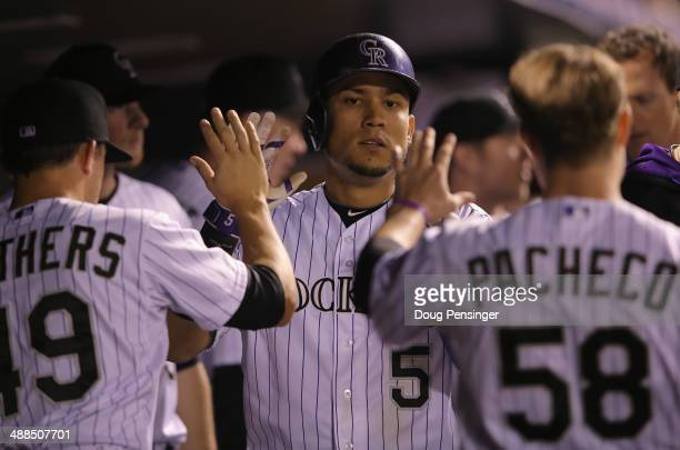 Carlos Gonzalez of the Colorado Rockies celebrates in the dugout with Rex Brothers and Jordan Pacheco after scoring on a double by Nolan Arenado of...