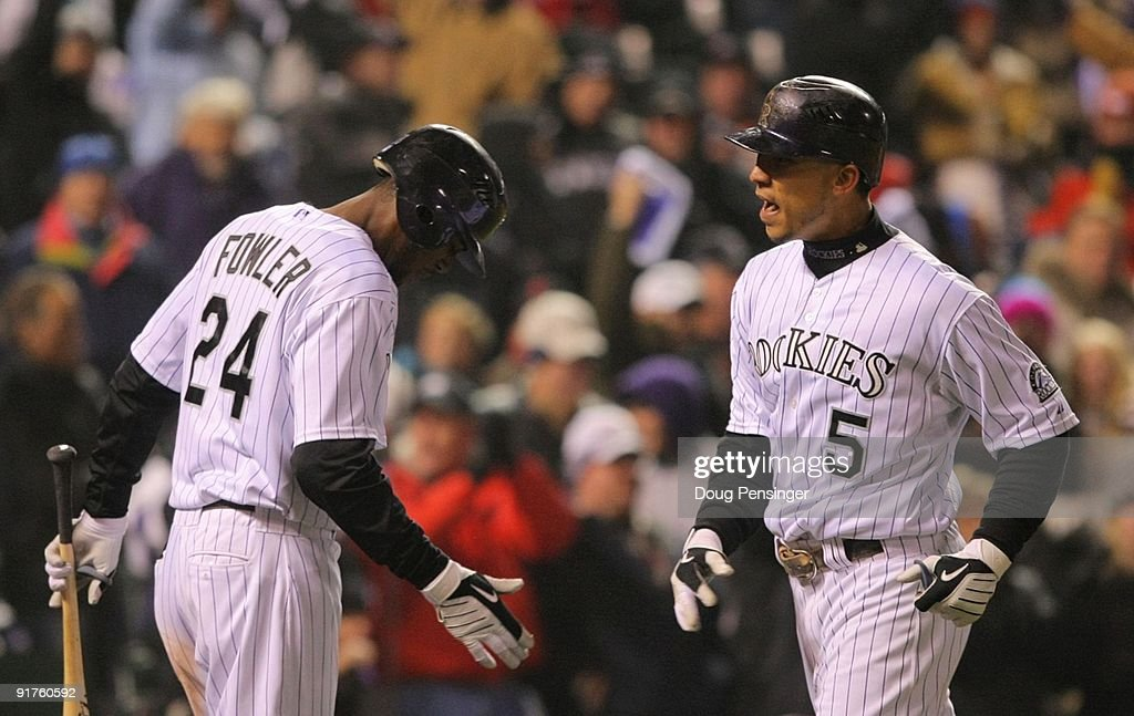 Carlos Gonzalez #5 of the Colorado Rockies celebrates with teammate Dexter Fowler #24 after hitting a game tying home run against the Philadelphia Phillies in the bottom of the fourth inning in Game Three of the NLDS during the 2009 MLB Playoffs at Coors Field on October 11, 2009 in Denver, Colorado.