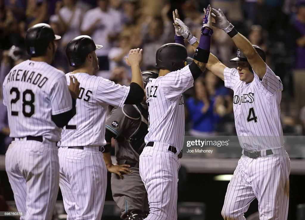 Carlos Gonzalez #5 of the Colorado Rockies congratulates Nick Hundley #4 of the Colorado Rockies at home plate after his grand slam home run against the Arizona Diamondbacks in the eighth inning that also scored Nolan Arenado #28 of the Colorado Rockies and Mark Reynolds #12 of the Colorado Rockies at Coors Field on September 2, 2016 in Denver, Colorado. The Rockies won 14-7.