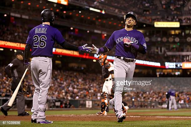 Carlos Gonzalez of the Colorado Rockies is congratulated by David Dahl after he scored on a single by Nolan Arenado of the Colorado Rockies in the...