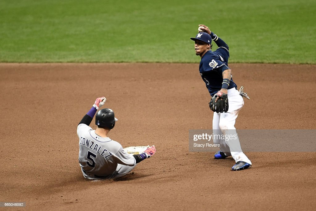 Carlos Gonzalez #5 of the Colorado Rockies is forced out at second base as Orlando Arcia #3 of the Milwaukee Brewers makes a throw to first base during the sixth inning of a game at Miller Park on April 5, 2017 in Milwaukee, Wisconsin.