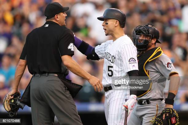 Carlos Gonzalez of the Colorado Rockies is restrained from going to the mound by home plate umpire Chad Fairchild in the sixth inning against the...