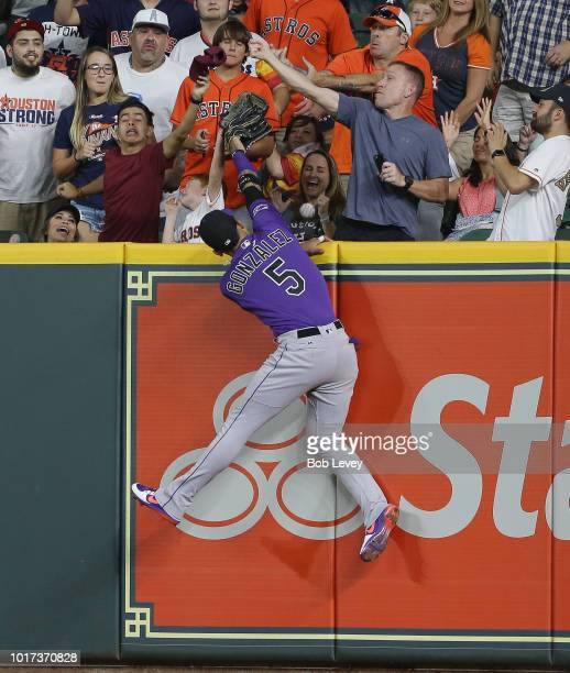 Carlos Gonzalez of the Colorado Rockies leaps at the wall but is unable to catch the home run ball hit by Evan Gattis of the Houston Astros in the...