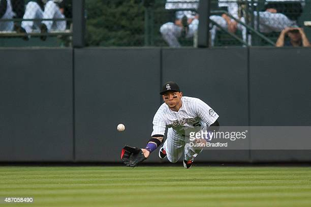 Carlos Gonzalez of the Colorado Rockies makes a diving catch in right field in the first inning of a game against the San Francisco Giants at Coors...