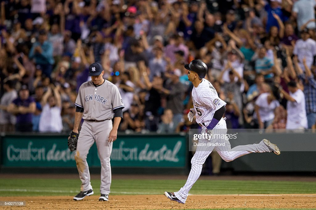 Carlos Gonzalez #5 of the Colorado Rockies rounds the bases after hitting an eighth inning solo homerun off of Conor Mullee #50 of the New York Yankees as Ike Davis #24 reacts during a regular season interleague game at Coors Field on June 14, 2016 in Denver, Colorado.