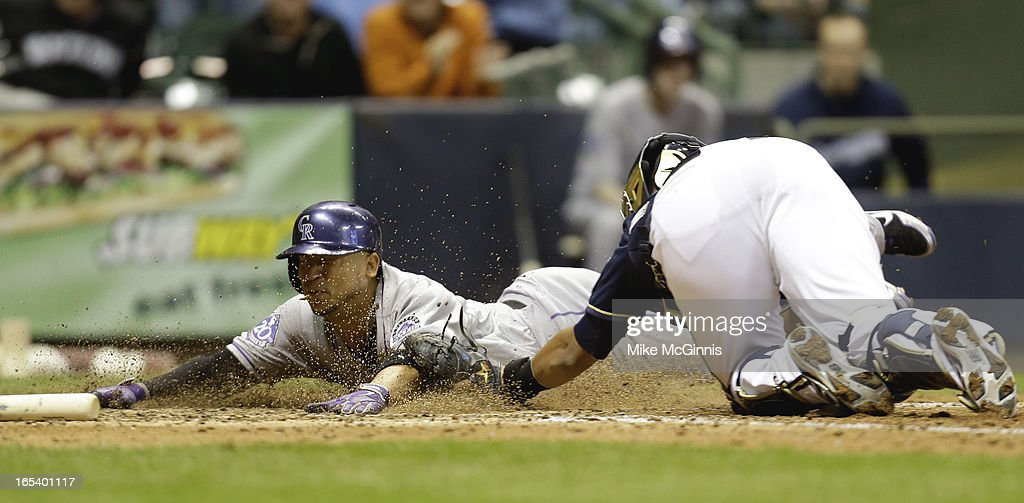 Carlos Gonzalez #5 of the Colorado Rockies slides head first into home plate while getting tagged out by Martin Maldonado #12 of the Milwaukee Brewers during the top of the 8th inning at Miller Park on April 3, 2013 in Milwaukee, Wisconsin.