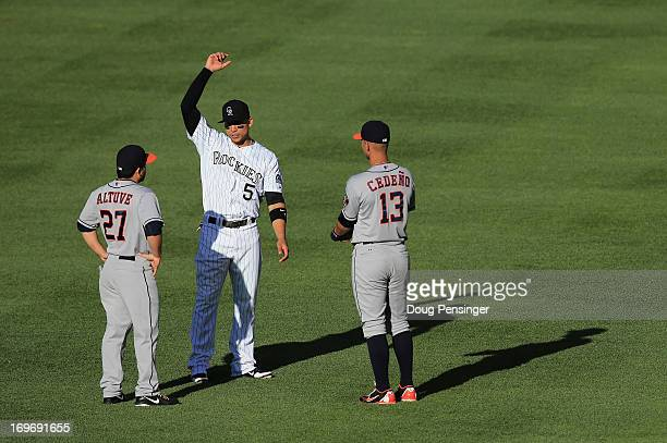Carlos Gonzalez of the Colorado Rockies talks with Jose Altuve of the Houston Astros and Ronny Cedeno of the Houston Astros as they warm up prior...