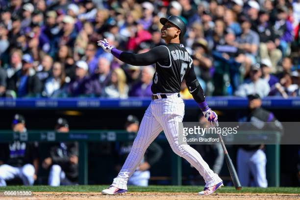 Carlos Gonzalez of the Colorado Rockies watches the flight of a fifth inning sacrifice fly ball that scored a run against the Los Angeles Dodgers at...