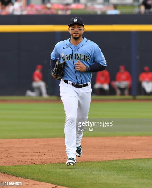Carlos Gonzalez of the Seattle Mariners runs in from right field against the Los Angeles Angels during a spring training game at Peoria Stadium on...