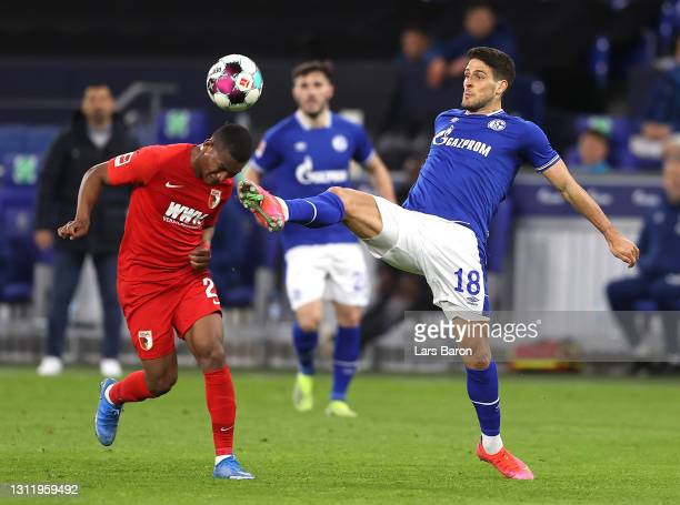 Carlos Gruezo of FC Augsburg is challenged by Goncalo Paciencia of FC Schalke 04 during the Bundesliga match between FC Schalke 04 and FC Augsburg at...