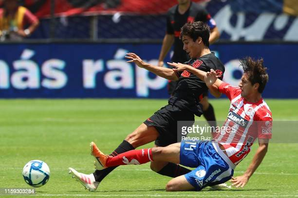 Carlos Gutiérrez of San Luis fights for the ball with Manuel Sanchez of Atletico de Madrid during the friendly match between Atletico San Luis and...