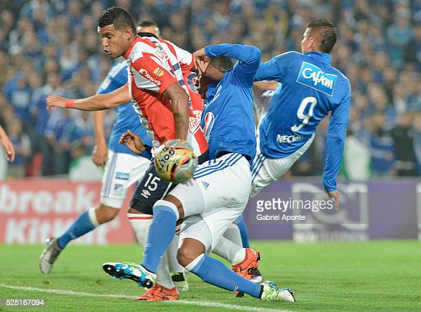 Carlos Henao of Millonarios struggles for the ball with Alexis Perez of Junior during a match between Millonarios and Junior as part of round 15 of...