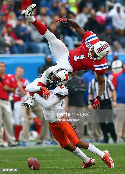 Carlos Henderson of the Louisiana Tech Bulldogs is tackled by Eaton Spence of the Illinois Fighting Illini on a pass play during the Zaxby's Heart of...