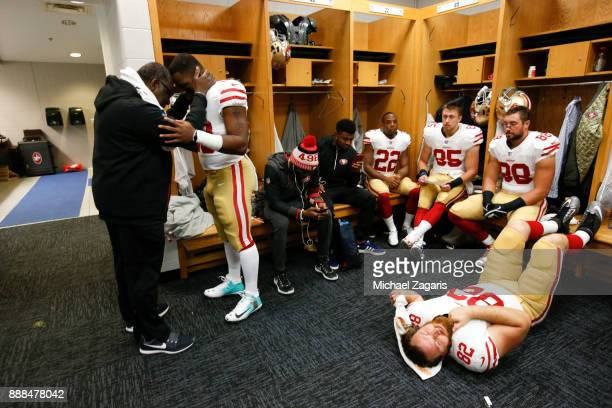 Carlos Hyde and Chaplin Earl Smith of the San Francisco 49ers share a moment in the locker room prior to the game against the Chicago Bears at...