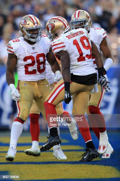 Carlos Hyde and Kendrick Bourne congratulate Aldrick Robinson of the San Francisco 49ers on his touchdown during the second half of a game against...