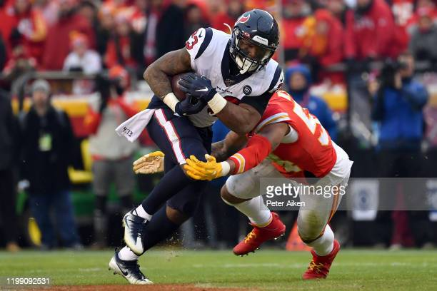 Carlos Hyde of the Houston Texans is tackled by the defense of the Kansas City Chiefs during the AFC Divisional playoff game at Arrowhead Stadium on...