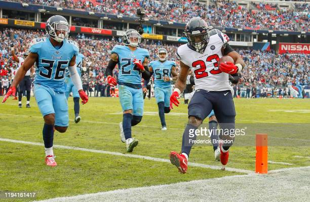 Carlos Hyde of the Houston Texans runs into the end zone for a touchdown against LeShaun Sims of the Tennessee Titans during the second half at...
